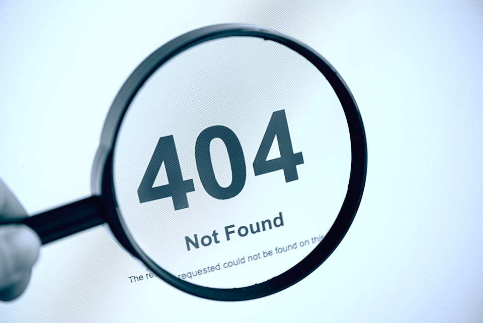 Image of person holding a magnifying glass over web page with crawling error as it says 404 Not Found