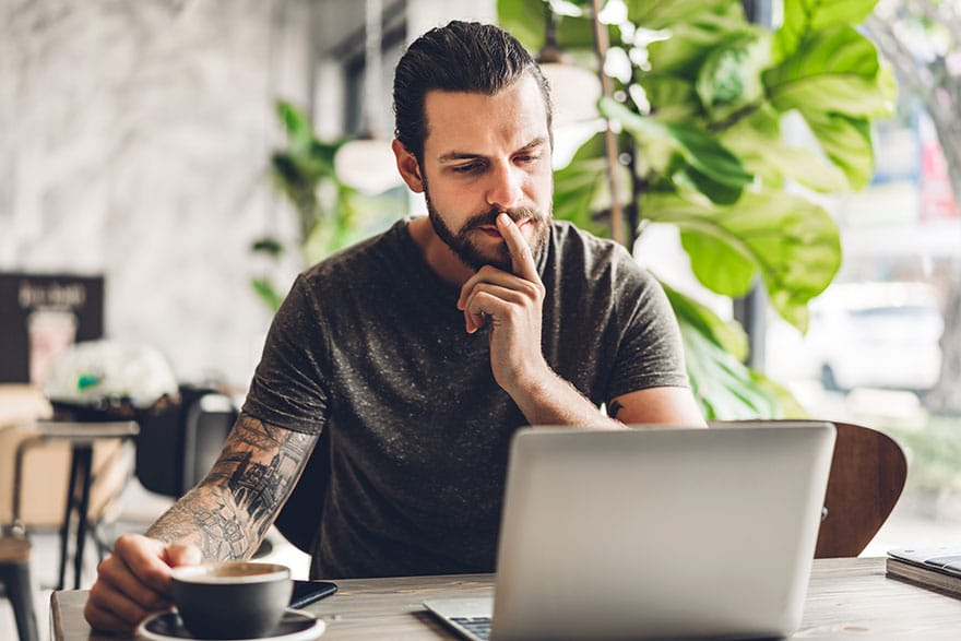 Picture of a man sitting behind a laptop with a finger on his chin to show that he is thinking